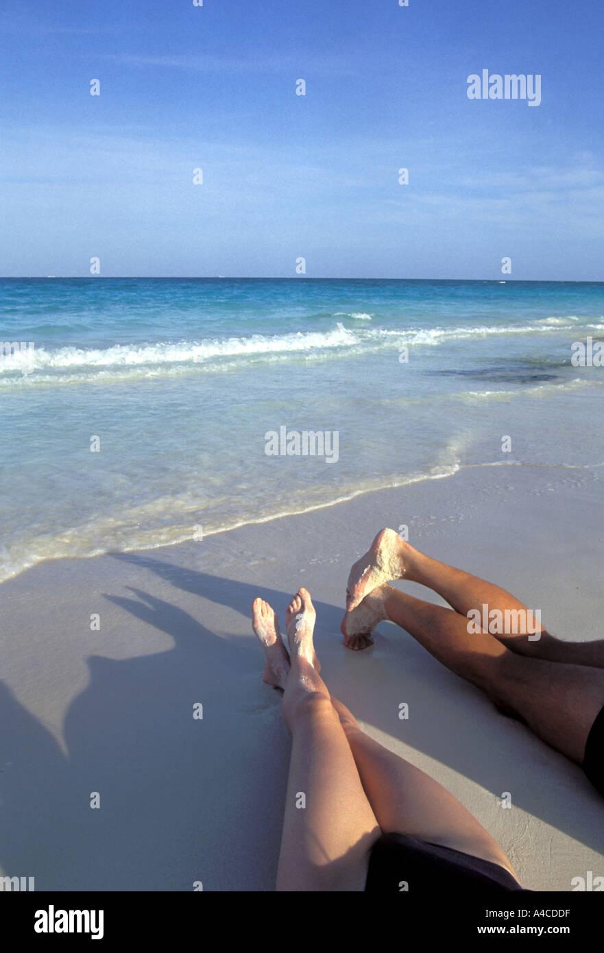 Paare Beine ausgestreckt am Strand mit Meer im Hintergrund