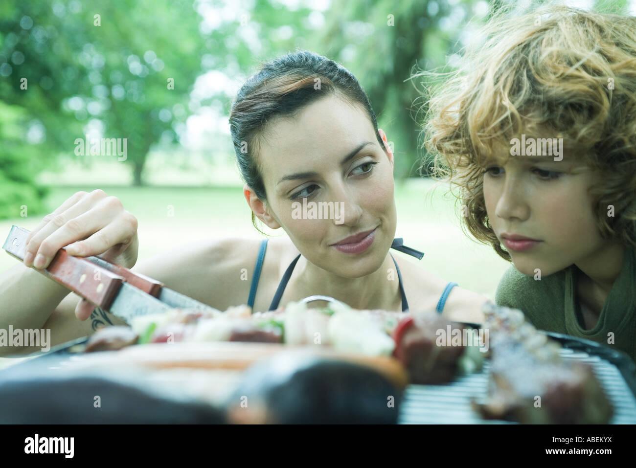 Boy Fleisch kochen am Grill, Frau mit einem Blick auf ihn