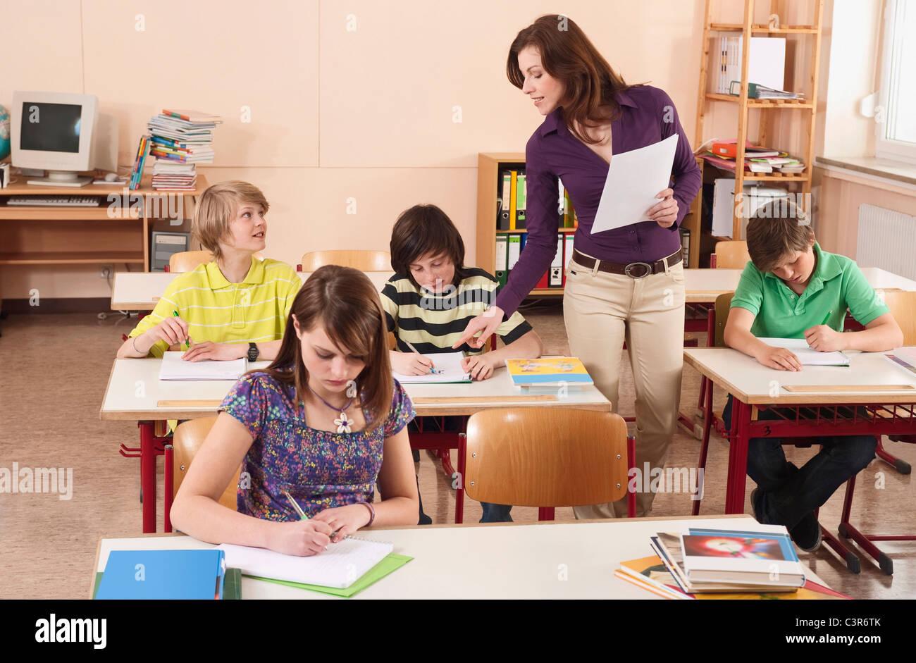 Deutschland, Emmering, Mädchen schreiben mit Lehrer