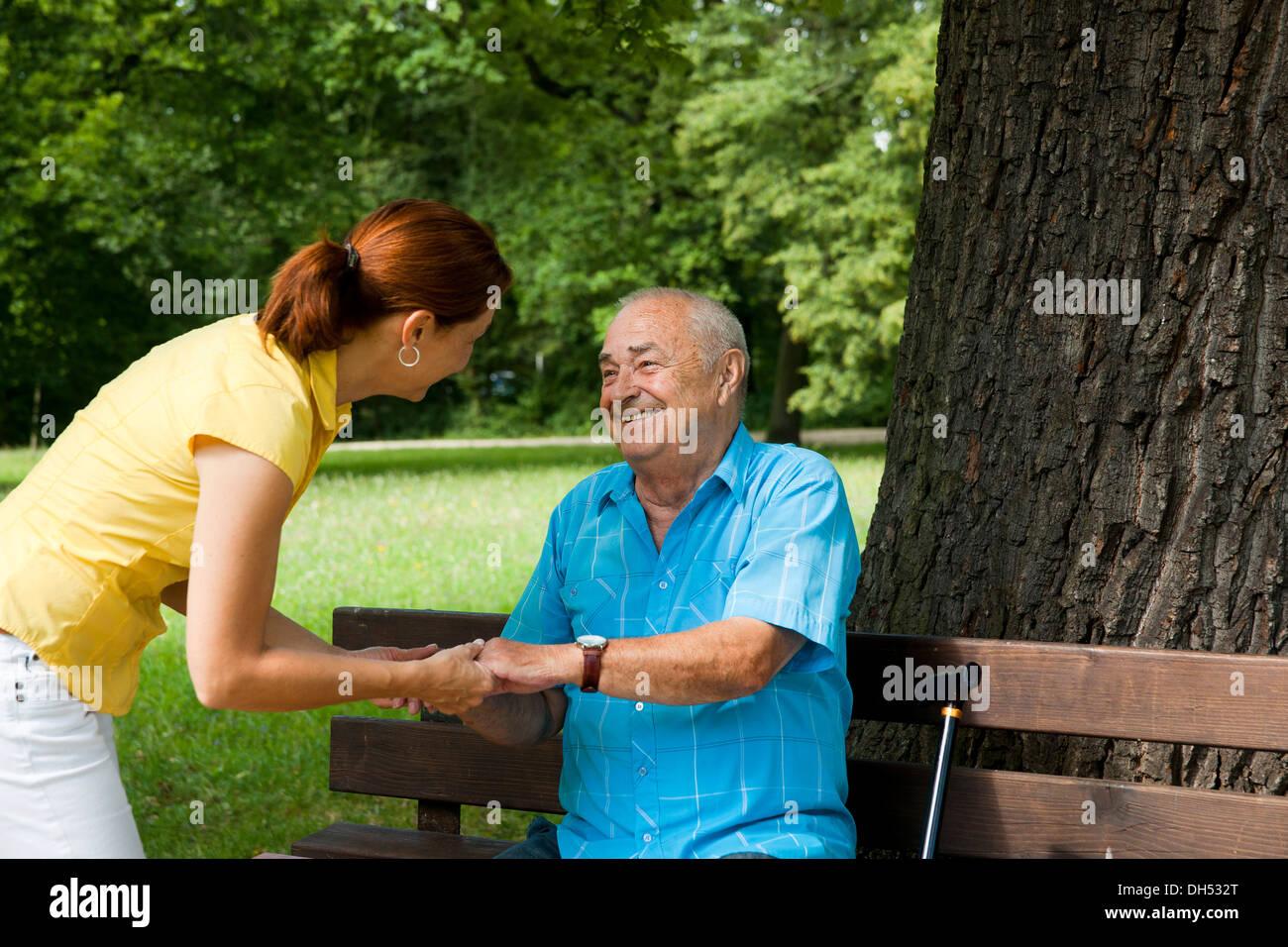 Frauen auf der Suche nach ein älterer Mann sitzt auf einer