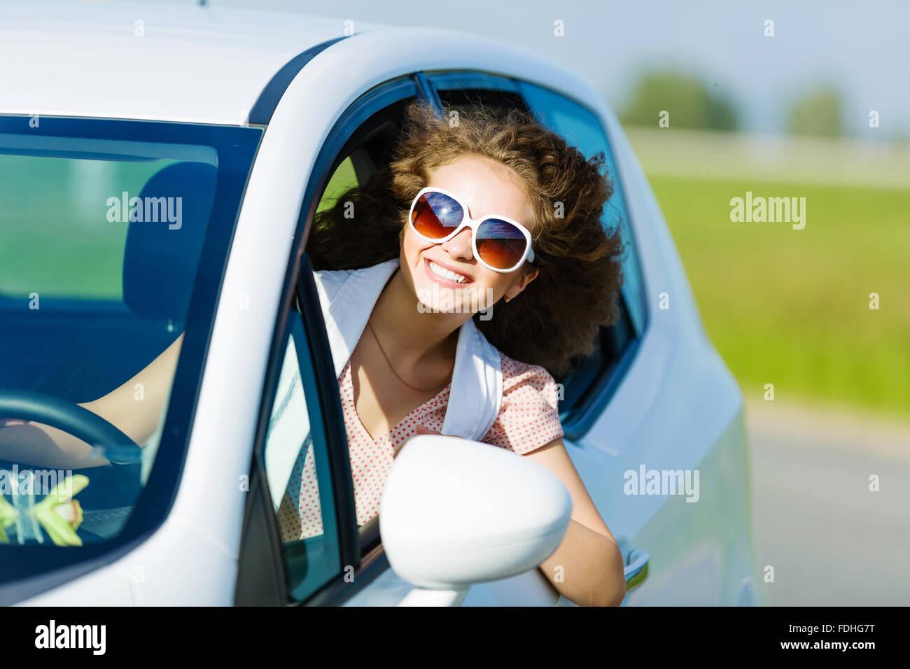 Junge hübsche Frau, Auto zu fahren und aus Autofenster