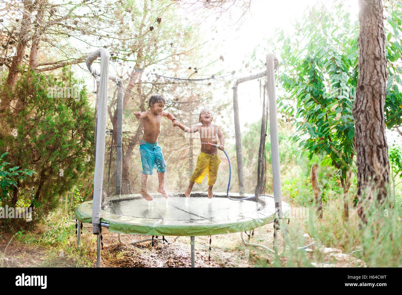 Zwei kleine Jungs beim Spritzen mit Wasser aus
